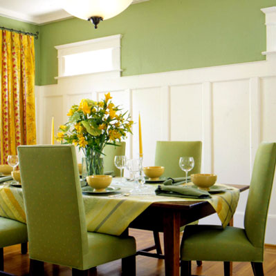 A green themed dining room with flat panel wainscoting