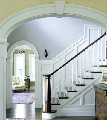 Stairs with wainscoting as seen through an archway