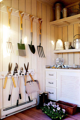 Several gardening tools hanging on a wall
