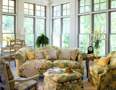 A sun room with couches and chairs in a floral pattern